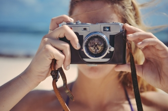 Image of a girl holding up a camera showing one of the best ways to explore NJ